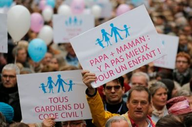 Protestors hold placards and balloons during a demonstration against a draft law to allow same-sex marriage in Paris