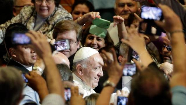 Pope Francis is surrounded by people taking pictures as he arrives for a meeting with representatives of civil society at the San Jose school stadium in Asuncion, Paraguay, Saturday, July 11, 2015. The pontiff is in Paraguay for three days, the last stop of his South American tour. (AP Photo/Gregorio Borgia)