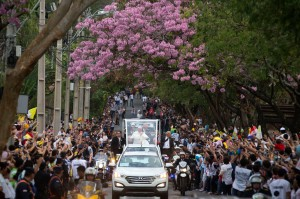 People line the street where Pope Francis passes in his popemobile as he makes his way to the Leon Condu stadium for an event in Asuncion, Paraguay, Saturday, July 11, 2015. Pope Francis lauded the strength and religious fervor of Paraguayan women on Saturday while visiting the country's most important pilgrimage site, where thousands of his fellow Argentines joined with hundreds of thousands of local faithful to welcome Latin America's first pope. (AP Photo/Victor R. Caivano)