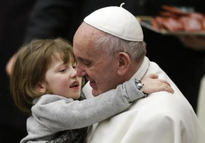 Pope Francis holds a child as he leads the weekly audience in Paul VI's hall at the Vatican January 20, 2016. REUTERS/Max Rossi