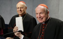Cardinal Schönborn holding up the exhortation next to Cardinal Lorenzo Baldisseri, secretary general of the synod.