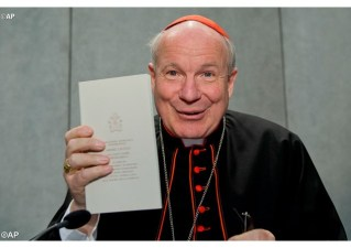 Cardinal Schönborn of Vienna holds up a copy of Pope Francis's document on family love, Amoris Laetitia. The new dicastery will be responsible for promoting and implementing its insights.